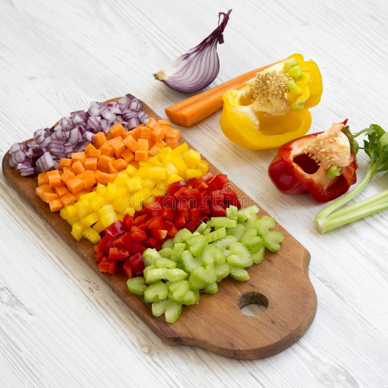 Chopped fresh vegetables carrot, celery, onion, colored peppers arranged on a cutting board on a white wooden background, side. View royalty free stock images