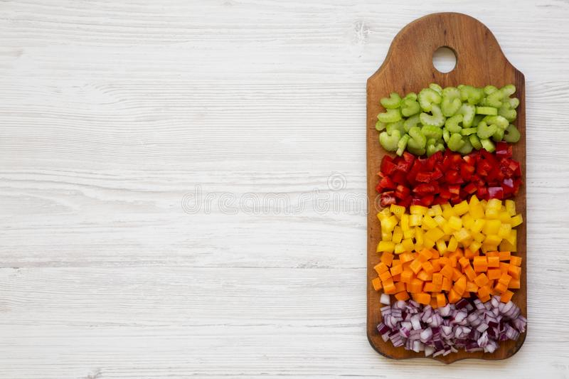 Chopped fresh vegetables carrot, celery, red onion, colored peppers arranged on cutting board on a white wooden background, stock photography