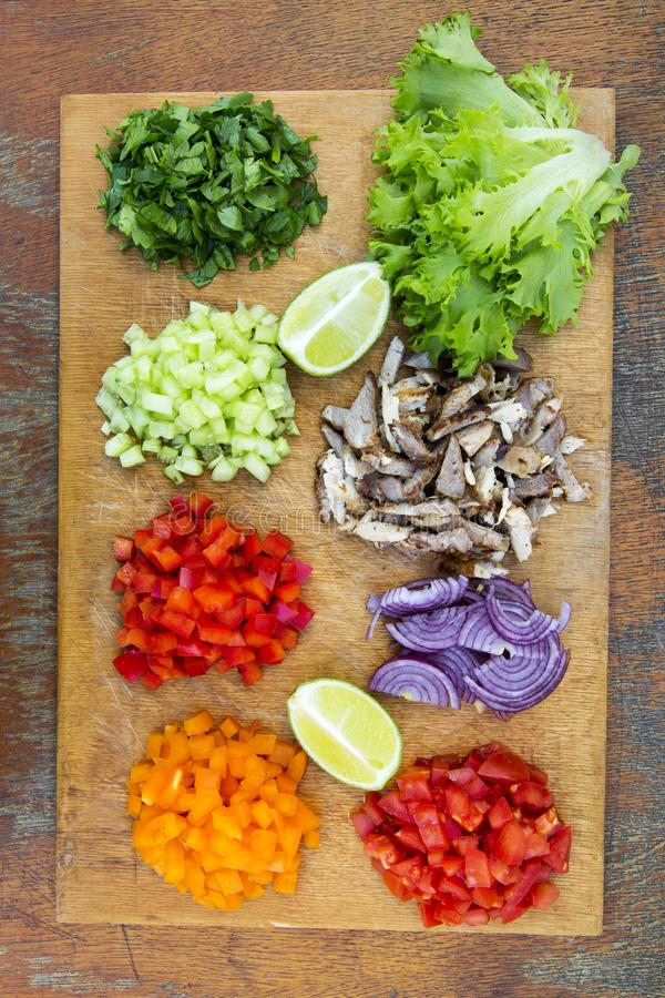 Chopped fresh vegetables with lime and beef on rustic wooden board. Tacos ingredients. Top view. From above. Flat lay, overhead. Chopped fresh vegetables with stock photo