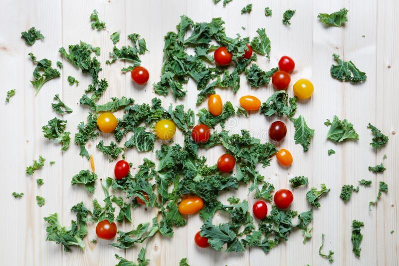 Chopped green kale with red and yellow plum cherry tomatoes royalty free stock image