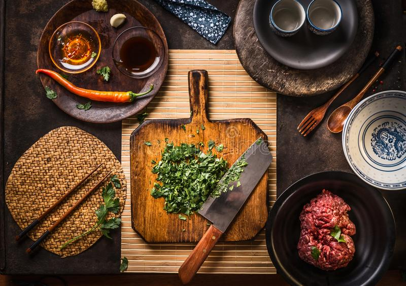 Chopped herbs on wooden cutting board with knife on dark rustic table background with kitchen utensils, bowls, plates and. Ingredients: Mincemeat, chili and soy stock photos