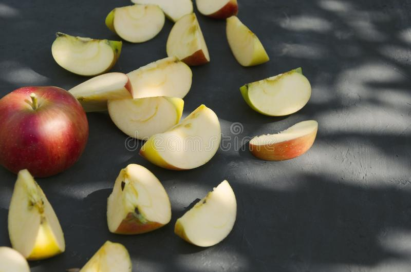 Chopped juicy apples on the dark surface, leaves shadow and autumn harvest. Tasty and juicy apples, autumn leaves on the dark surface Chopped juicy apples on the stock image