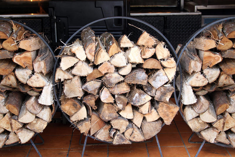 Chopped logs. Stacks of cut or chopped logs in wire hoop frames stock photos
