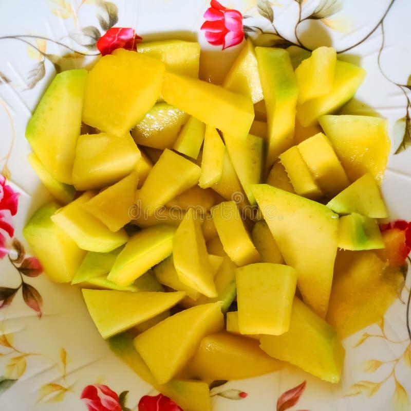 Chopped mango on a plate. Delicious tropical fruit stock photos