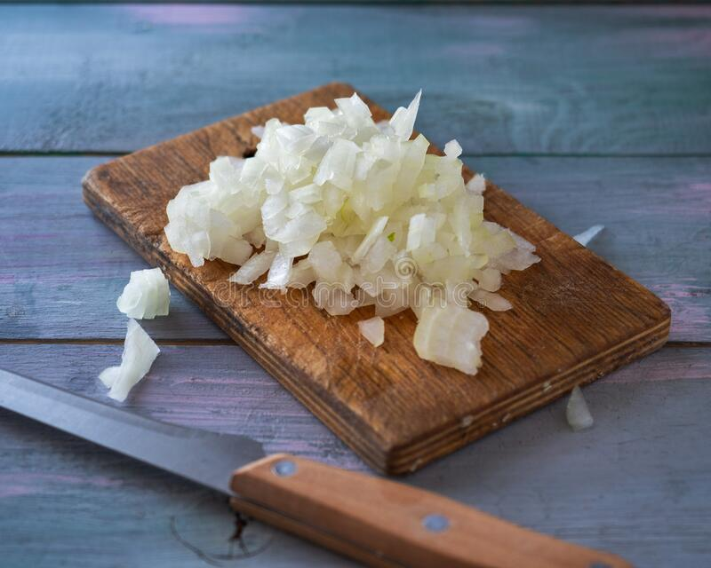 Chopped onions on a cutting board and a kitchen node lie on a wooden table. Cooking blank stock images