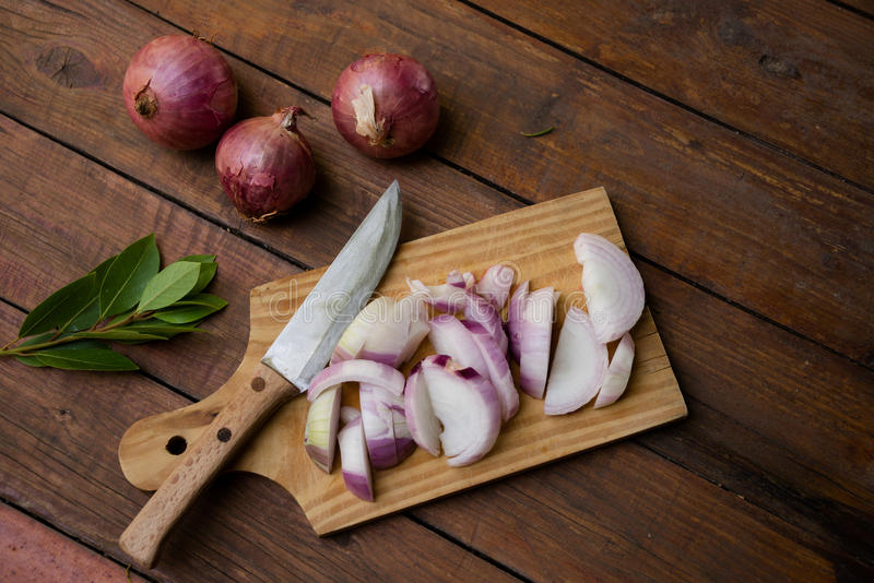 Chopped onions. And knife on wooden chopping board, laurel leaves , on a nice rustic background stock photo