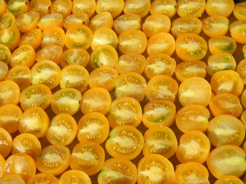 Chopped organic yellow tomatoes ready for drying, abstract background. Chopped organic yellow tomatoes ready for drying. Abstract background stock photo