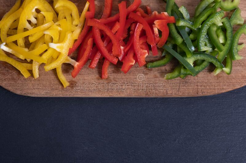 Chopped paprika and pepper on a wooden board. On a black background royalty free stock photo