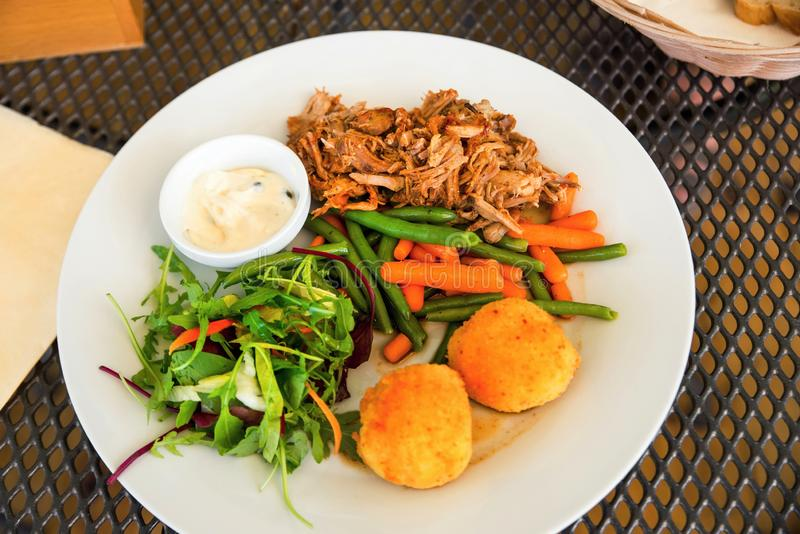 Chopped pork, croquettes, rucola salad and mayonnaise. Chopped pork meat, potato croquettes and rucola leaf salad on white plate with small bowl with mayonnaise royalty free stock photos