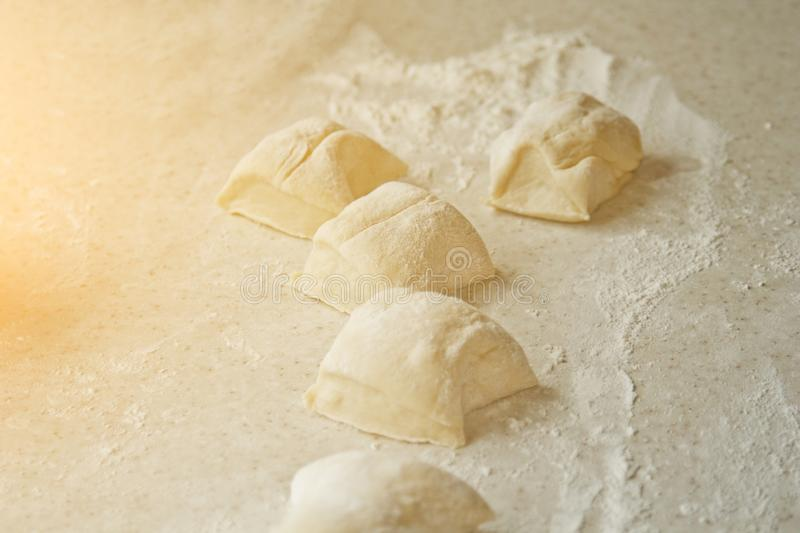 Chopped raw kneaded dough into pieces on the table against the background of the kitchen interior. cooking baking dish royalty free stock images