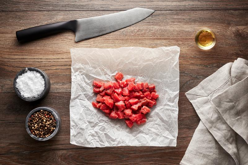 Chopped raw veal meat cubes for meat stew on white cooking paper and wooden table stock images