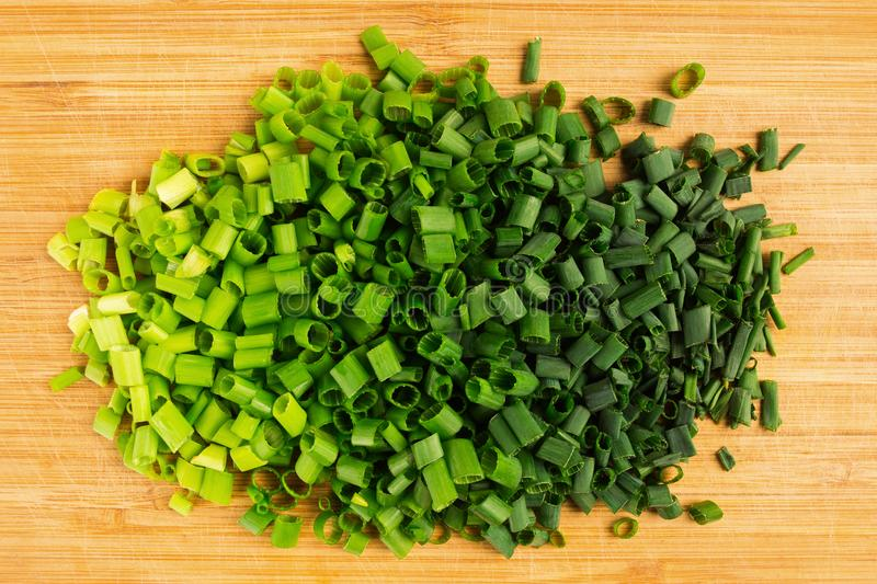 Chopped spring onion on the wooden board, green color gradation. Overhead view royalty free stock image