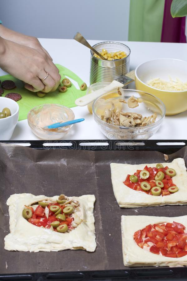 Chopped sweet peppers and olives on pizza puff pastry. The ingredients are placed on the table. The dough lies on the baking sheet.  stock images