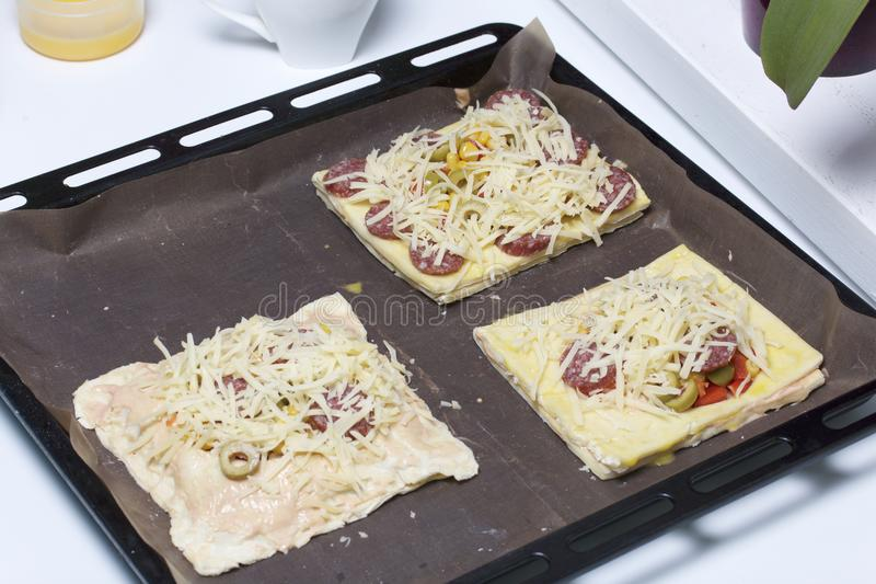 Chopped sweet peppers and olives on pizza puff pastry. The ingredients are placed on the table. The dough lies on the baking sheet.  stock photos