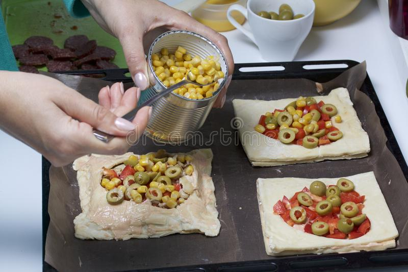 Chopped sweet peppers and olives on pizza puff pastry. A woman puts corn on pizza. The ingredients are placed on the table. The do. Ugh lies on the baking sheet stock images