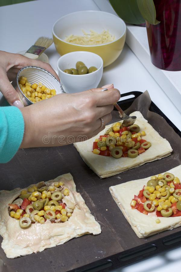 Chopped sweet peppers and olives on pizza puff pastry. A woman puts corn on pizza. The ingredients are placed on the table. The do. Ugh lies on the baking sheet stock image