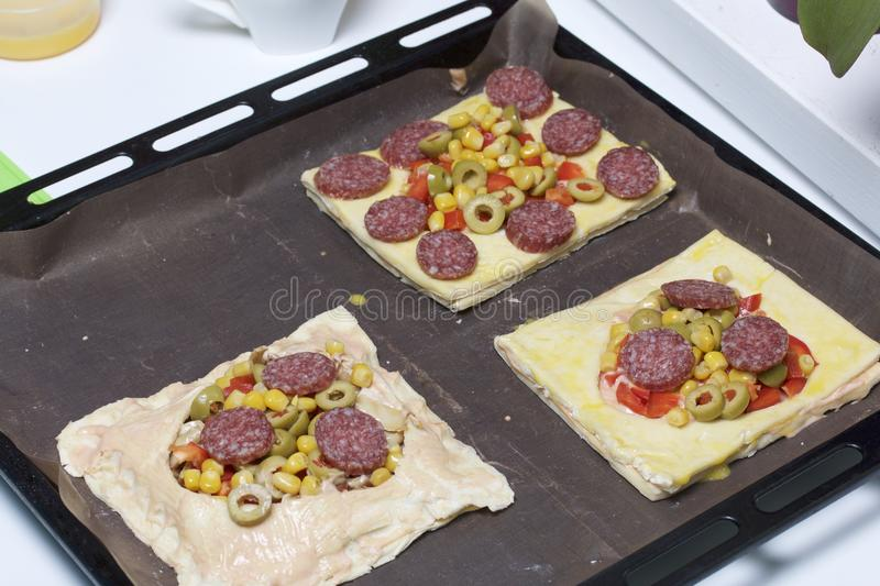 Chopped sweet peppers, salami and olives on pizza puff pastry. The ingredients are placed on the table. The dough lies on the baki. Ng sheet royalty free stock photo