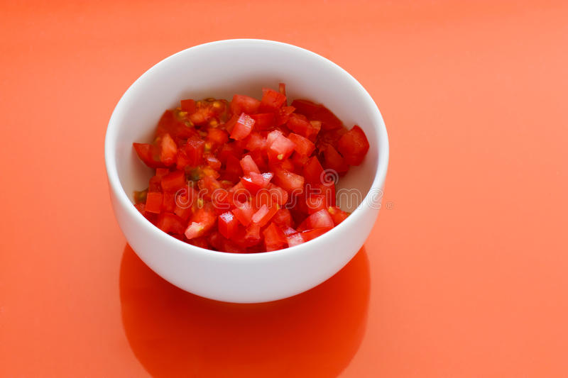 Chopped Tomatoes. White bowl with chopped tomatoes and an orange background stock photo
