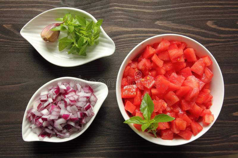 Chopped tomatoes. Bowls with chopped raw tomatoes and onions on tomato sauce royalty free stock image
