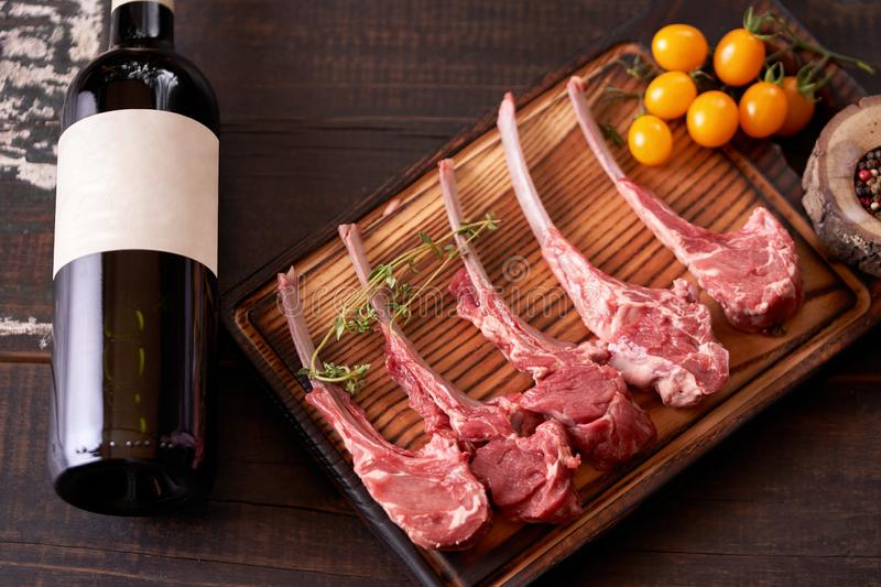 Chopped veal rib on a cutting board with a bottle of red wine on a wooden background. Multi-colored peppers nearby. Top view at an angle stock image