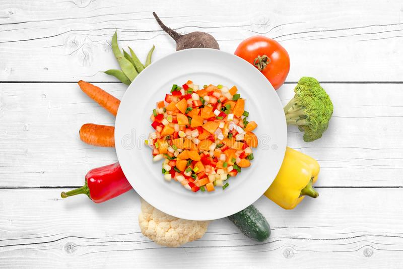 Chopped vegetables on plate. Fresh organic vegetables in plate background on white wooden cuisine table stock photography