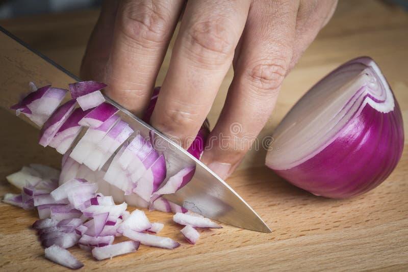 Choppig del cocinero una cebolla roja con un cuchillo imagenes de archivo