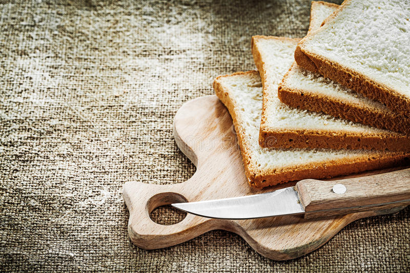 Chopping board kitchen knife sliced bread on hessian background.  royalty free stock images