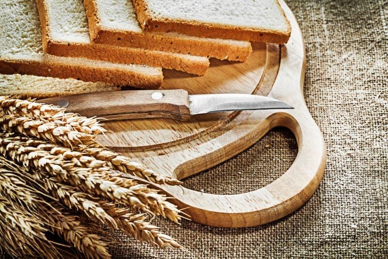 Chopping board kitchen knife sliced bread rye ears on hessian ba. Ckground royalty free stock image