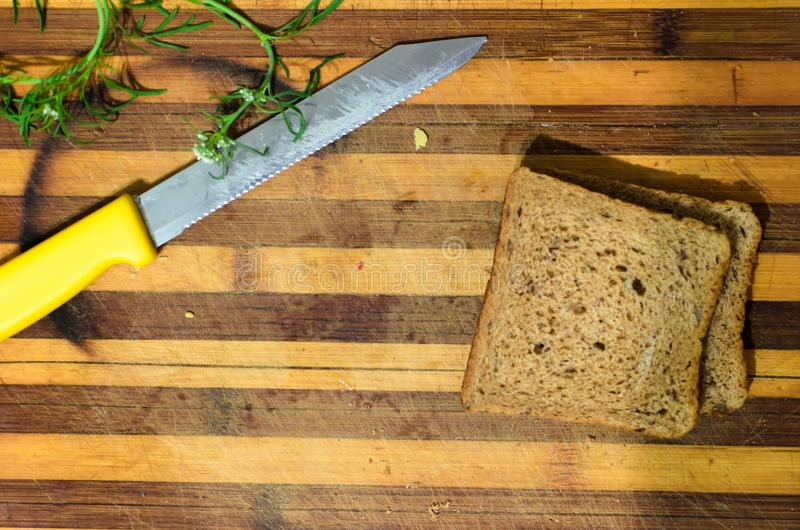Chopping board with knife, bread and greens stock image