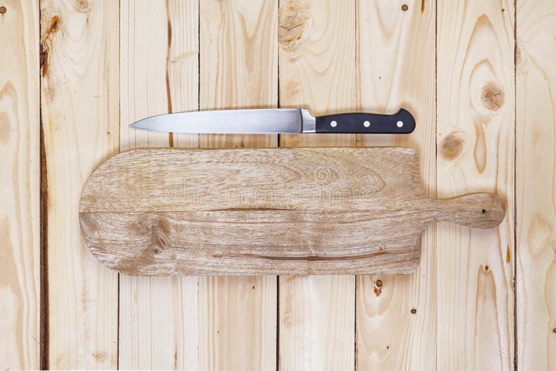 Chopping board with knife on wooden table top view royalty free stock photo