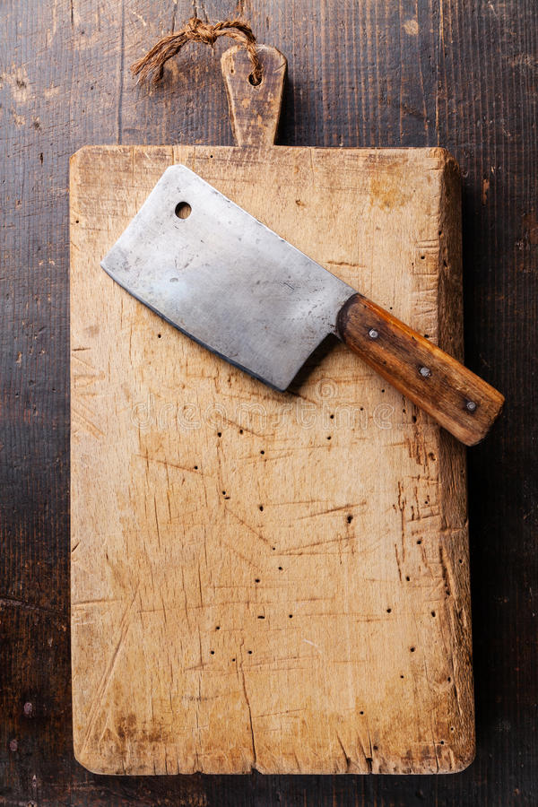 Chopping board and Meat cleaver. On dark wooden background royalty free stock images