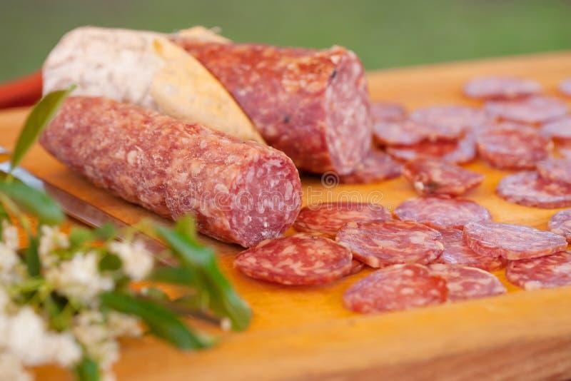 Chopping board of salami stock image