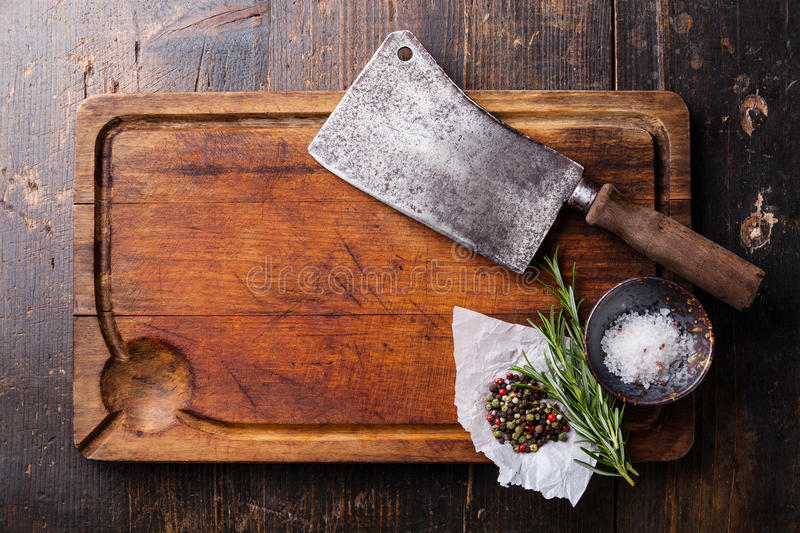Chopping board, seasonings and meat cleaver. On dark wooden background stock image