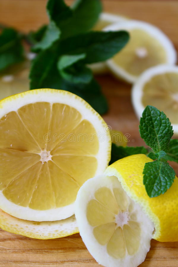 On the chopping board. Yellow lemon with fresh sprig of mint. royalty free stock images