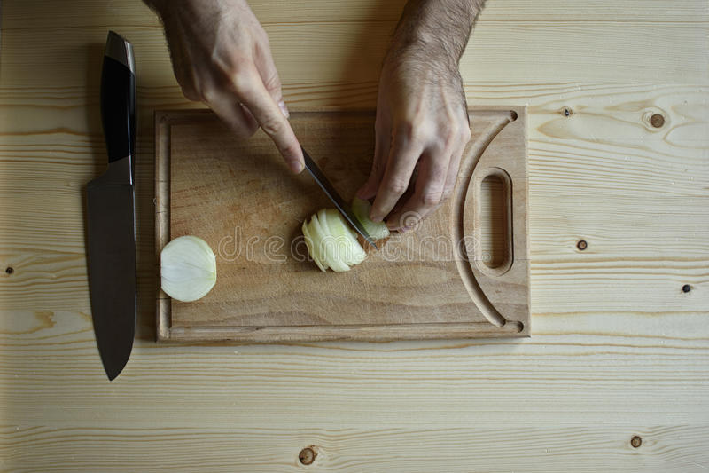 Chopping. A man chopping onion on a wooden board stock images