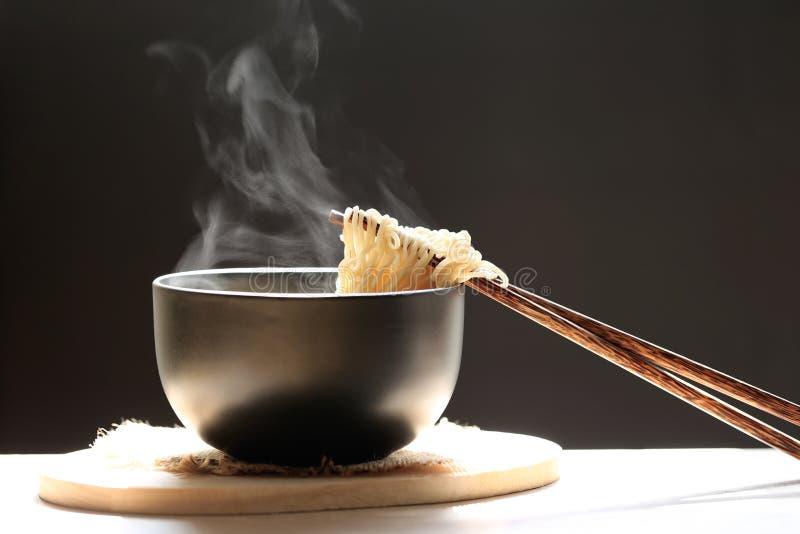 Chopsticks με τα στιγμιαία νουντλς στο φλυτζάνι με το σκοτεινό BA αύξησης καπνού στοκ εικόνες