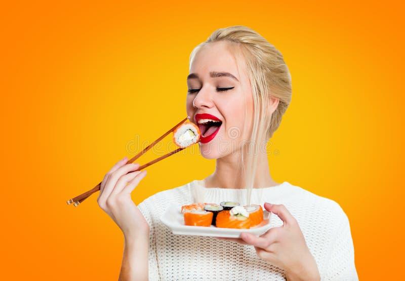 chopsticks που κρατούν τις νεολαίες γυναικών σουσιών στοκ εικόνα με δικαίωμα ελεύθερης χρήσης