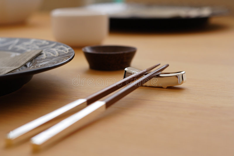 Chopsticks. Wood & chrome chopsticks on table set for dinner stock photography