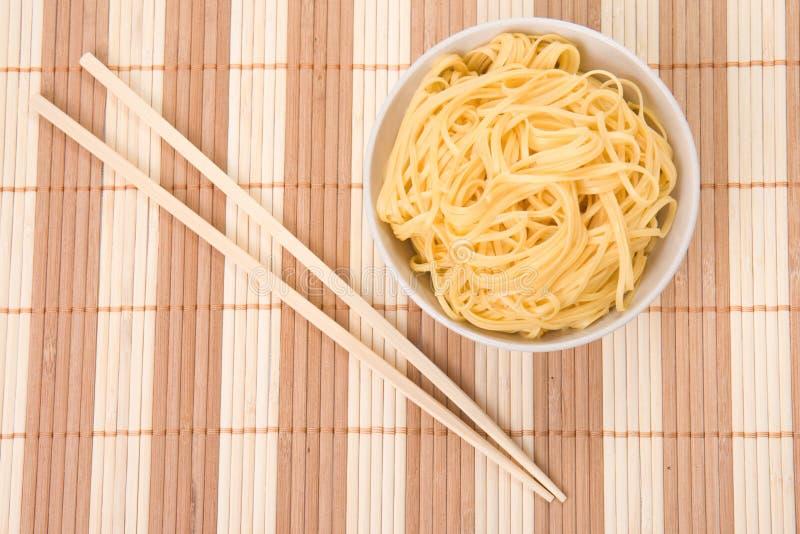 Chopsticks, bacia e macarronetes imagem de stock
