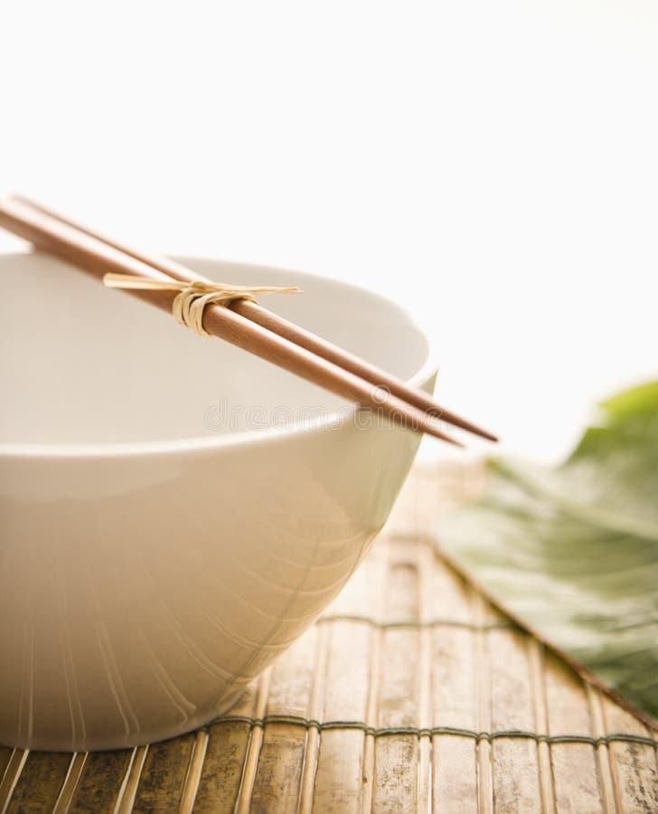 Chopsticks em uma bacia vazia. Isolado imagens de stock