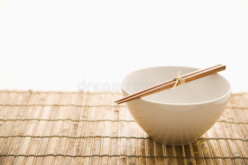 Chopsticks em uma bacia vazia. Isolado fotos de stock