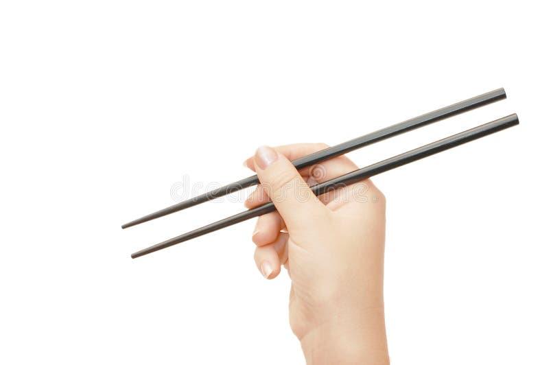 Chopsticks em uma mão imagens de stock royalty free