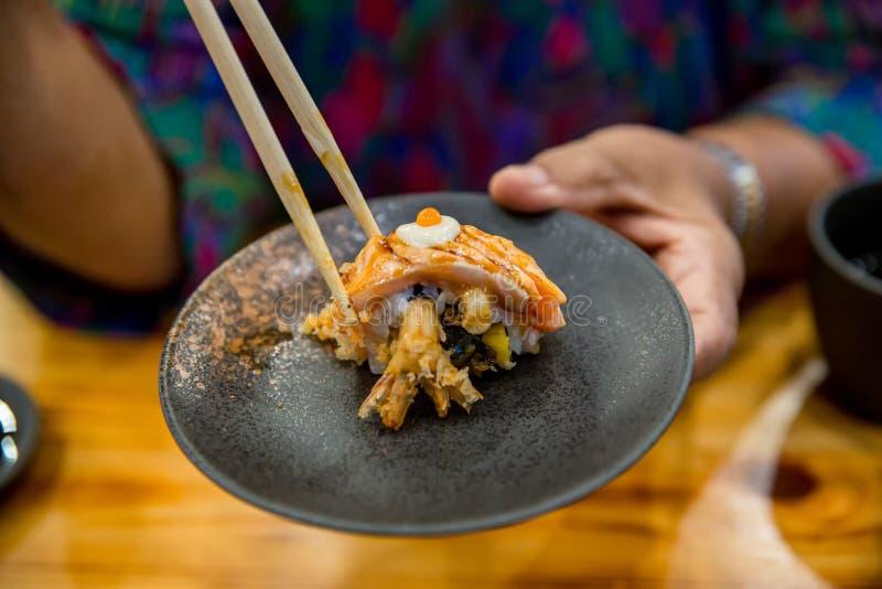 chopsticks hold on sushi fresh salmon. Japanese food for healthy. salmon sushi, egg salmon sushi premium menu. royalty free stock photo
