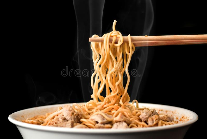Chopsticks pick up tasty noodles with smoke on dark background. Ramen in white bowl. royalty free stock images