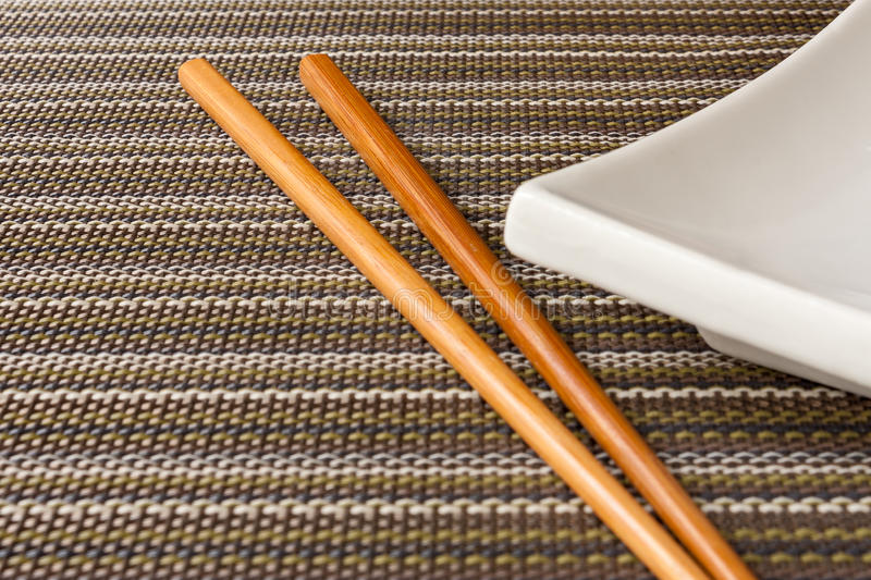 Chopsticks and plate on texture background royalty free stock image