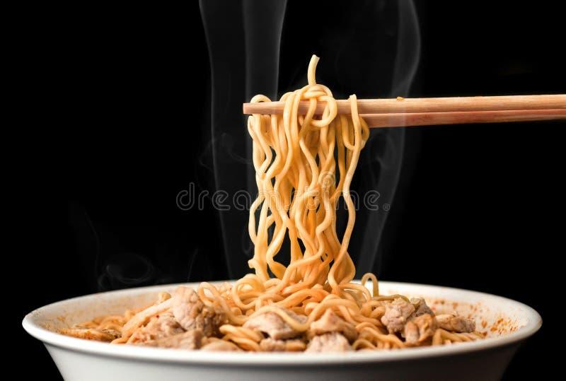 Chopsticks podnoszą up smakowitych kluski z dymem na ciemnym tle Ramen w białym pucharze obrazy royalty free