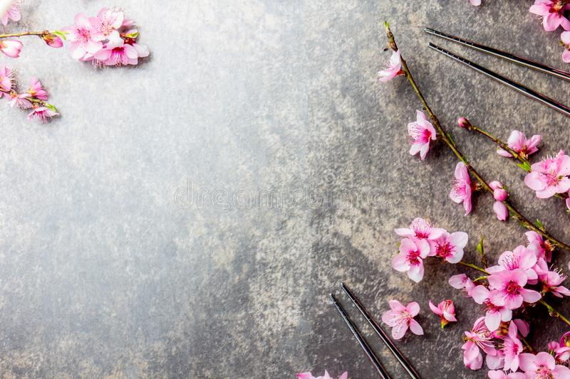 Chopsticks and sakura branches on gray stone background. Japanese food concept. Top view, copy space. stock photo