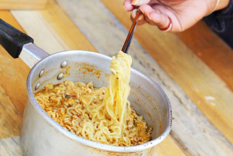 Chopsticks trzyma azjatykcich kluski w garnku zdjęcia stock
