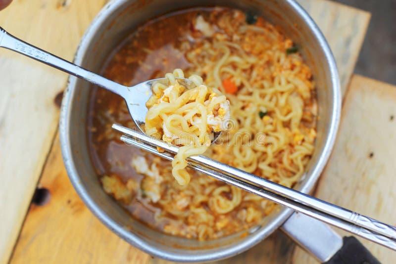 Chopsticks trzyma azjatykcich kluski w garnku zdjęcia royalty free