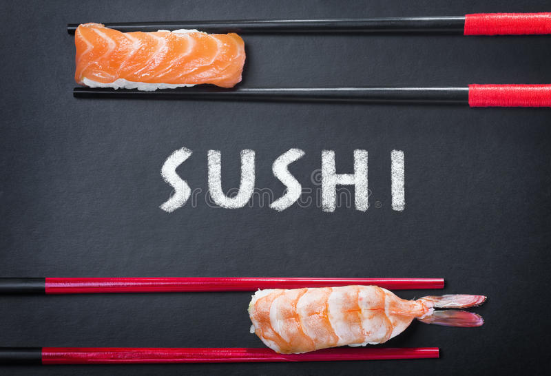 chopsticks and two sushi and an inscription on a black background royalty free stock images